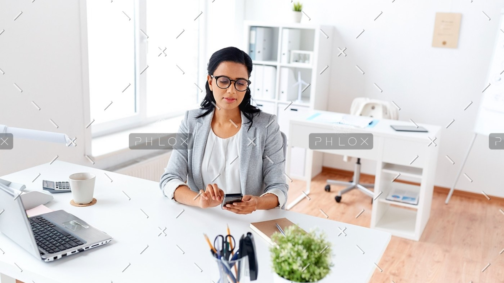 businesswoman-messaging-on-smartphone-at-office-P5AQU8Y